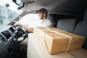 Delivery driver driving van with parcels on seat outside the warehouse